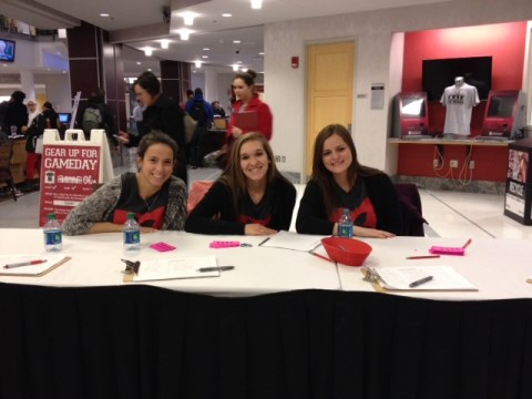 Staff members Analiese, Olivia, and Emily work the sign-in table